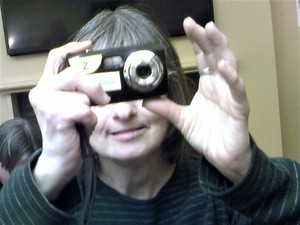 A photographer holds a camera up, snapping an image, the camera covering her eyes.